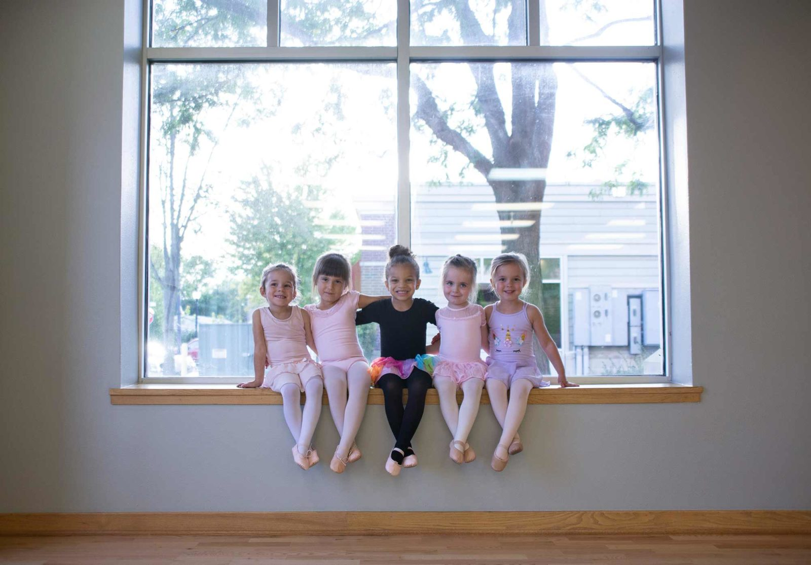 Young dancers sitting on a window ledge
