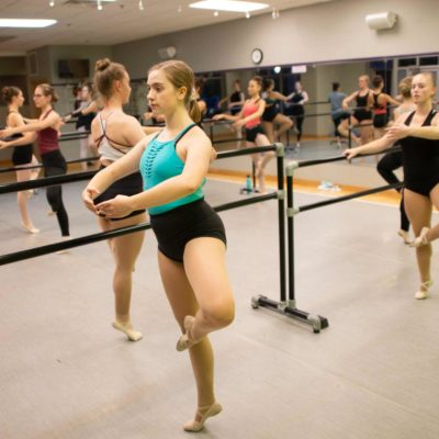 Ballet dancers practice using a bar